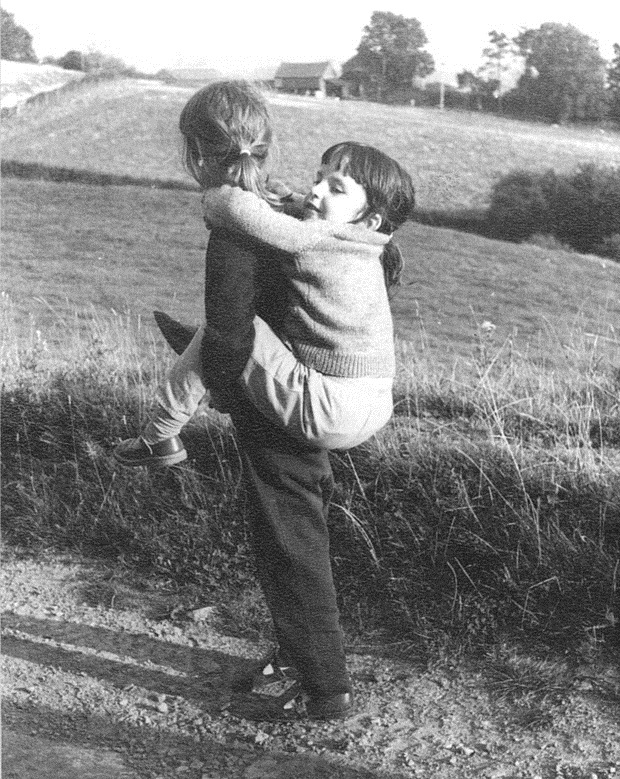 Ruth Thomas aged about five, being given a piggy-back by her sister Ann.