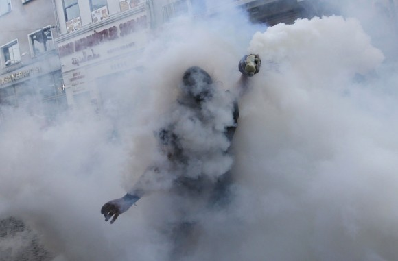 Protestor throws back tear gas canister