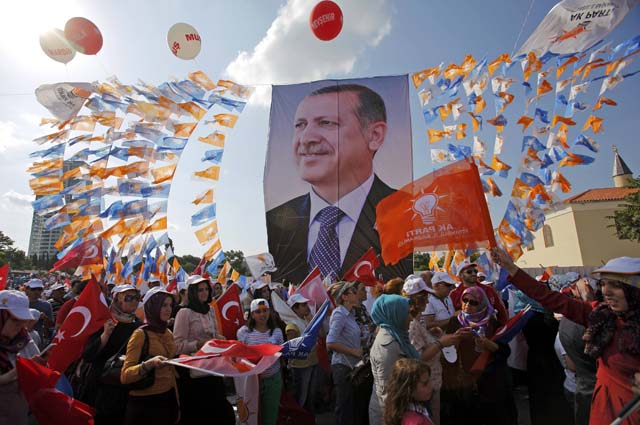 Supporters hold a poster of Turkish PM Erdogan during a rally of ruling AK party in Istanbul
